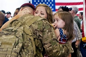 A soldier hugs his wife and daughter