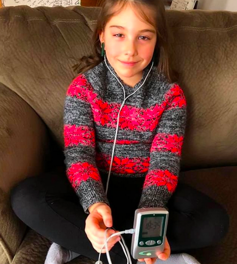 A young girl uses Alpha-Stim