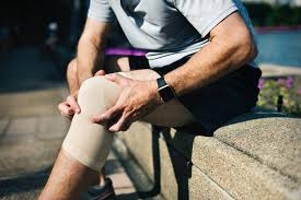 A man holds his knee in pain