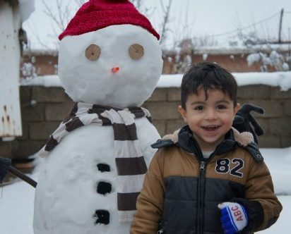 A young boy stands next to a snowman