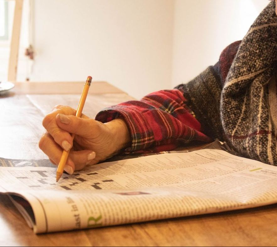 A hand is seen working on a crossword puzzle